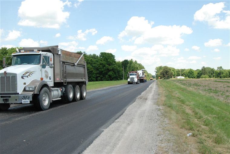 Big trucks on a small road doing some asphalt paving in Leesburg, IN